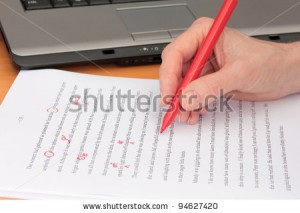 stock-photo-hand-proofreading-a-manuscript-beside-laptop-94627420