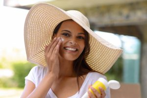 Woman wearing a floppy hat and applying sunscreen.